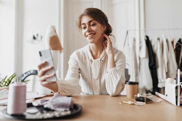Positive woman in beige blouse holds phone and sits in office