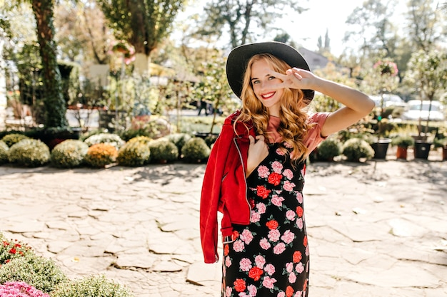 Positive woman in black sundress with floral print, suede jacket and hat shows peace sign and poses in garden.