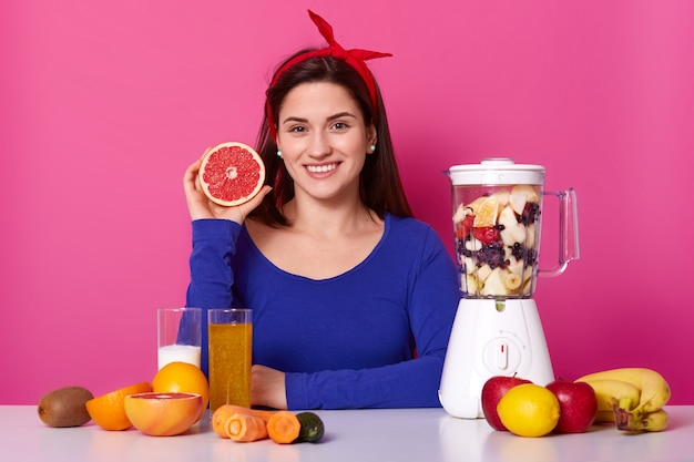 Positive woman in blue jumper and headband, prepares healthy juice, uses fresh ingredients, adds cut fruits in blender jar, holds slice of grapefruit likes smoothie in morning. vegeterian food concept