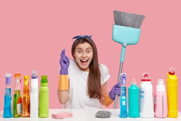 Donna positiva in abiti casual, incrocia le dita, crede nel lavoro di finitura sulla casa, porta scopa, indossa guanti di gomma, circondata da materiale per la pulizia