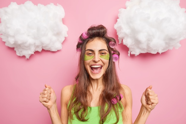 ポジティブな女性が拳を握り締める何かが適用されることを祝う目の下の緑の美しさのパッチは、ピンクの壁に隔離された自分自身を治療する素晴らしいヘアカットをしたい