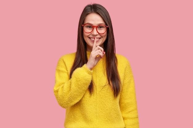 La donna positiva dimostra il gesto di silenzio, tiene l'indice sulle labbra, vestita con abiti casual, pettegola con il migliore amico, racconta informazioni segrete