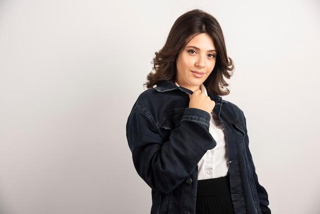 Donna positiva in giacca di jeans in piedi su bianco.