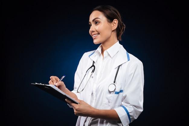 Scrittura positiva di medico della donna in lavagna per appunti e guardare da parte