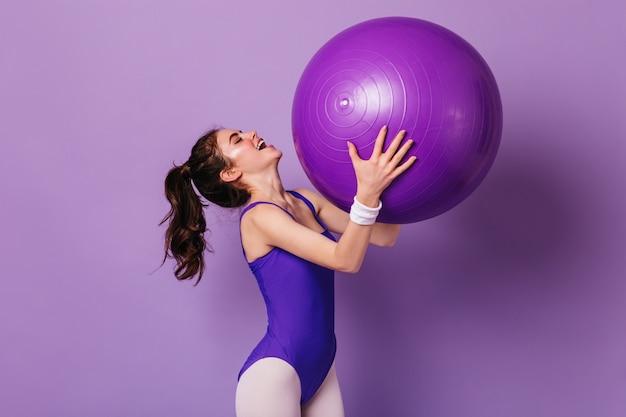 Positive woman doing aerobics on purple wall