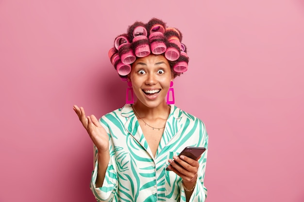 Positive woman dressed in silk slumber suit uses mobile phone downloads new application makes curly hair with rollers isolated over pink wall