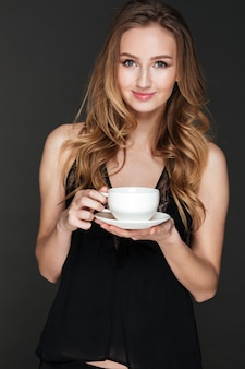 Positive woman drinking coffee and posing