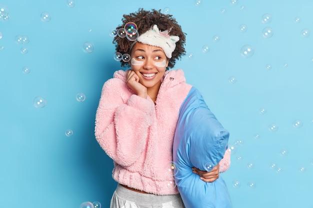 La donna positiva gode del tempo per il riposo vestita in pigiama caldo indossa la maschera del sonno sulla fronte le toppe di bellezza pone con il cuscino contro le bolle di sapone della parete blu intorno
