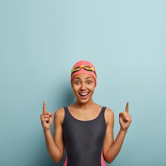 Positive woman enjoys water sport, dressed in black swimsuit, swimming hat and goggles, points above on free space, advertises accessories for diving, prepares for contest. sport and promotion concept