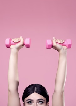 Positive woman exercising with dumbbells