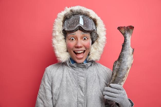 따뜻한 재킷을 입고 겨울철 낚시를하러가는 긍정적 인 여성은 스노우 보드 고글을 착용하고 저온에서 활동적인 휴식을 취합니다.