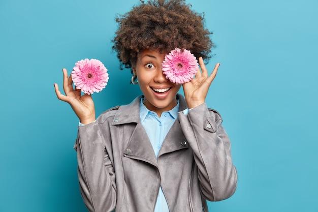 Позитивная женщина с вьющимися волосами закрывает глаза розовыми герберами, дейзи носит серый пиджак и рубашку, изолированную над синей стеной, прячет красивые глаза двумя розовыми цветами