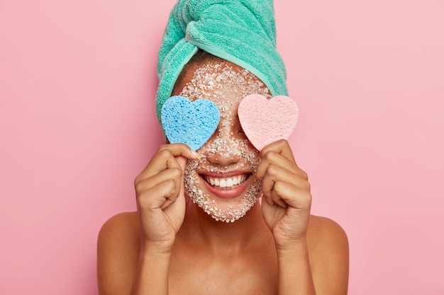 Positive woman has fun during beauty treatments, keeps two heart shaped sponges on eyes, has broad smile, shows white teeth, wrapped towel on head, poses indoor with naked body
