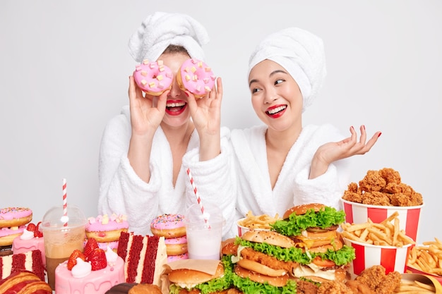 Positive woman has fun at home covers eyes with two doughnuts eats junk food together with best friend.