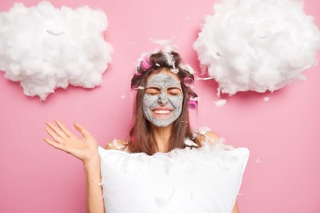 ポジティブな女性は楽しい気分を持っています手のひらを上げて目を閉じます枕の魚がローラーで髪型を作った後、周りにたくさんの羽があり、屋内でポーズをとります顔に粘土マスクを適用します