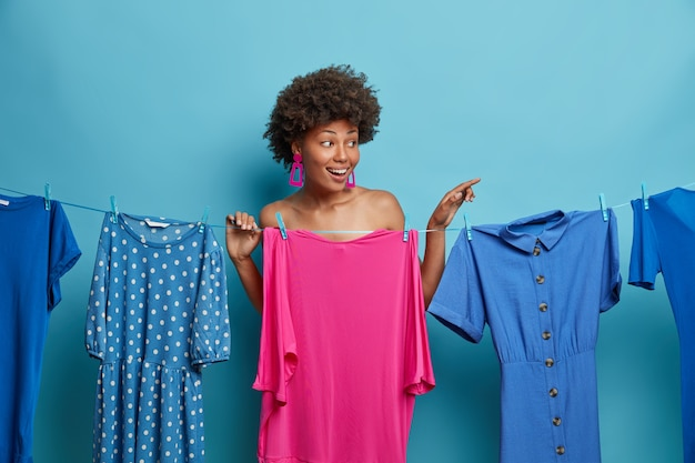 Positive woman has nothing to wear, waits until dresses drying on rope, stands undressed against blue wall, points index finger away, shows something, hides naked body. clothes and fashion