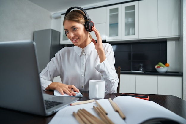 Positive woman in headphones having video chat on laptop