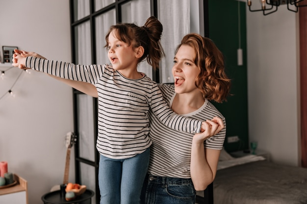 Positive woman and her daughter in striped t-shirts laugh and dance in apartment.