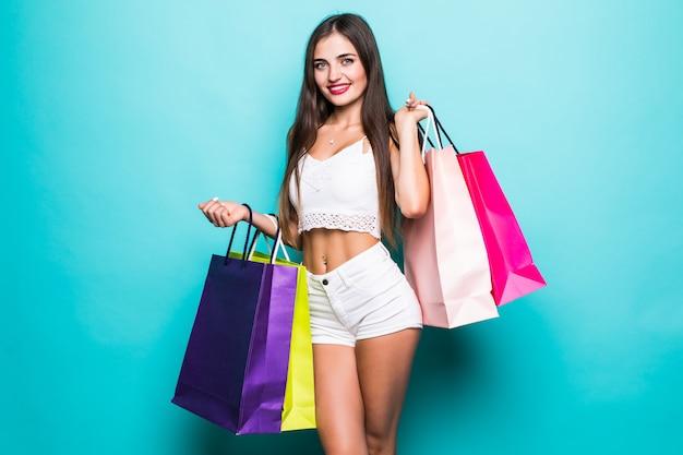Положительная женщина держит сумки покупки, изолированные над бирюзовым цветом стены