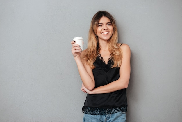 Положительная женщина держит чашку кофе