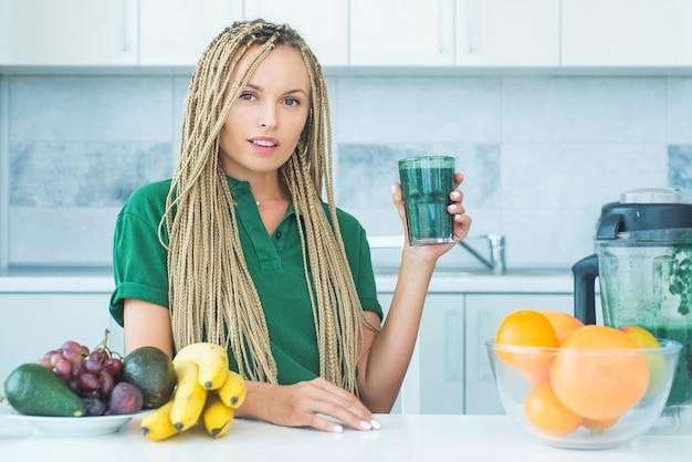 신선한 녹색 스무디 잔을 들고 긍정적 인 여자입니다.