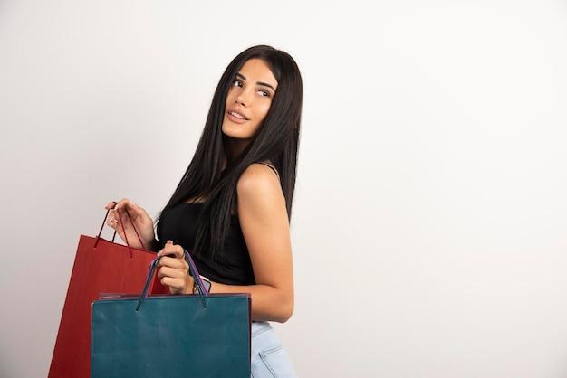 베이지 색 바탕에 쇼핑백을 들고 긍정적 인 여자입니다. 고품질 사진