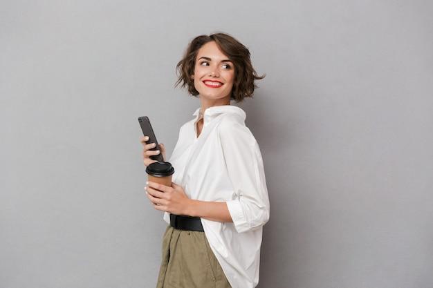 テイクアウトコーヒーを保持し、携帯電話を使用して、灰色の壁に隔離