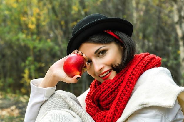 검은 모자와 빨간 스카프를 손에 든 긍정적인 여성은 미소를 지으며 카메라를 쳐다본다