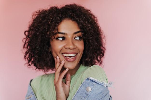Позитивная женщина в ярком топе улыбается на изолированной стене