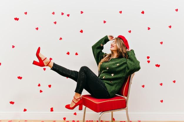 Позитивная женщина в зеленом свитере дурачится в студии, украшенной сердечками