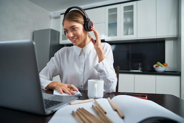Позитивная женщина в наушниках, имеющая видеочат на ноутбуке