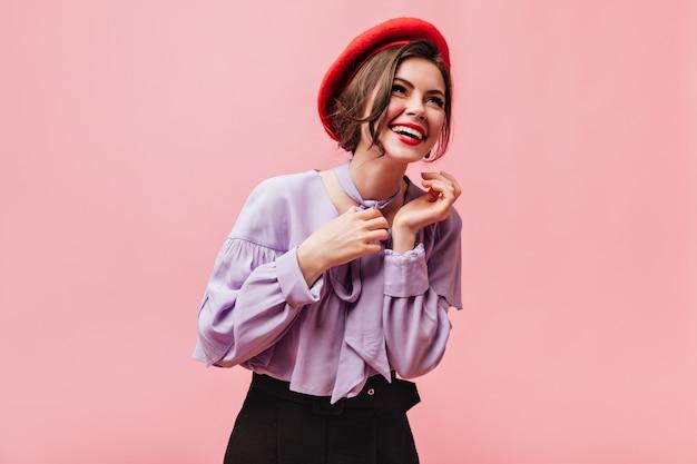 赤いベレー帽とライラックのブラウスのポジティブな女性はピンクの背景で笑います。
