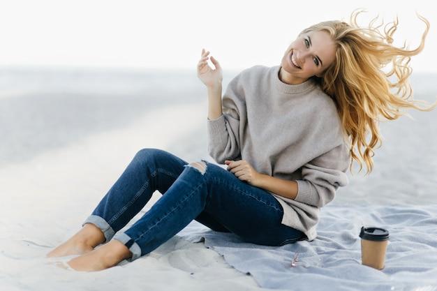Позитивная женщина в мягком свитере дурачится на пляже. открытый портрет очаровательной женской модели, сидящей в песке с чашкой чая.