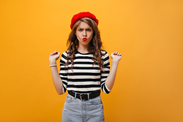 스트라이프 셔츠와 베레모에 긍정적 인 여성이 재미있는 얼굴을 만듭니다. 격리 된 배경에 포즈 넓은 블랙 벨트와 데님 스커트에 곱슬 젊은 아가씨.