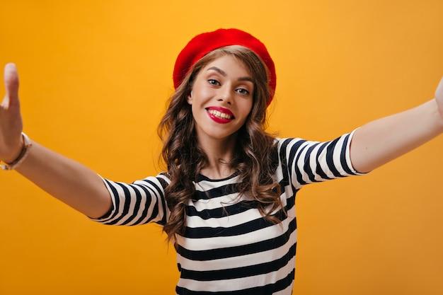 스트라이프 셔츠와 밝은 베레모에 긍정적 인 여성이 셀카를 만듭니다. 빨간 모자에 현대적인 헤어 스타일을 가진 멋진 어린 소녀는 격리 된 배경에 사진을 걸립니다.