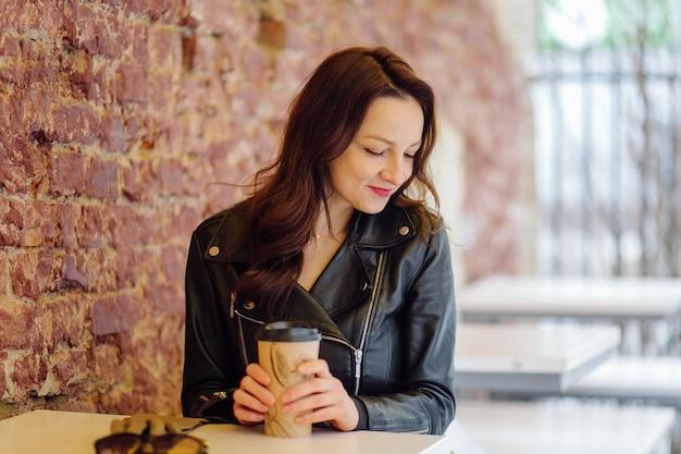 낮에 카페 근처 거리에 테이블에 앉아있는 동안 테이크 아웃 음료를 마시는 세련된 옷에 긍정적 인 여성