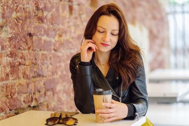 昼間カフェ近くの通りのテーブルに座ってテイクアウトの飲み物を飲むスタイリッシュな服を着たポジティブな女性