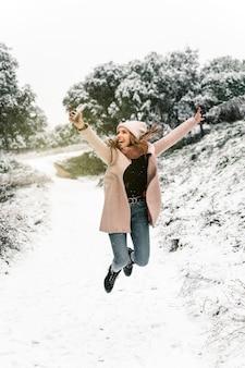 雪の降る冬の森で楽しみながら、スマートフォンでジャンプして自画像を撮る暖かい服を着たポジティブな女性