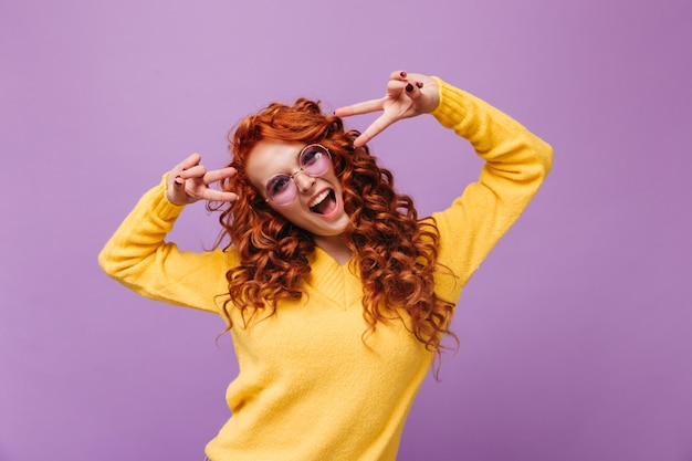 Позитивная женщина в желтом свитере и очках показывает знак мира и смеется на сиреневой стене