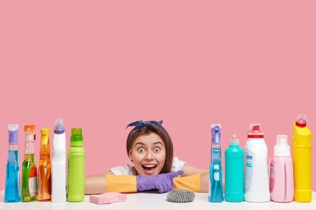 ポジティブな女性用務員はテーブルに寄りかかって、表情を大喜びし、洗剤を指しています