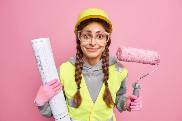 긍정적 인 여성 유지 보수 작업자가 건설 초안을 확인하여 집을 리모델링하기 위해 페인트 롤러를 사용하여 고객이 방을 재 장식하는 데 도움이되는 조끼를 반사하는 보호 안전모 투명 안경을 착용합니다.