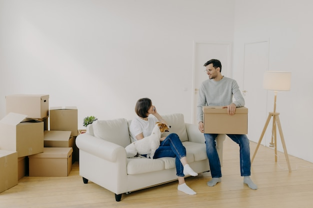 Positive woman and man pose in empty spacious room during relocation day