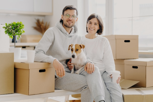 Positive woman and man pose near stack of cardboard boxes, pose for making portrait with dog, relocate in new living place, wear white casual clothes, pose in spacious kitchen with big windows
