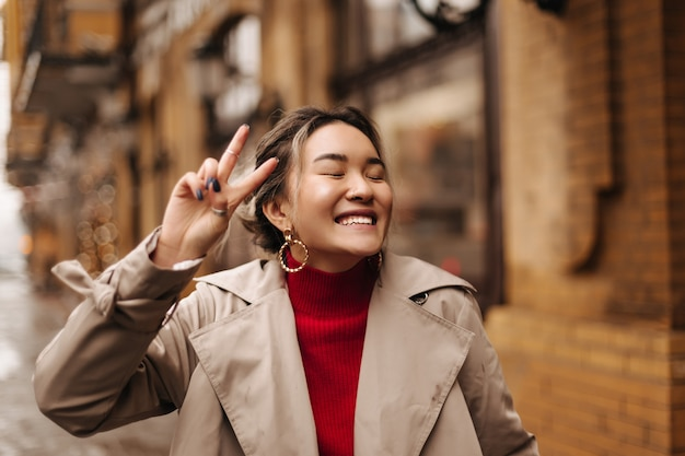 Positive woman in massive earrings laughing with closed eyes against wall of building