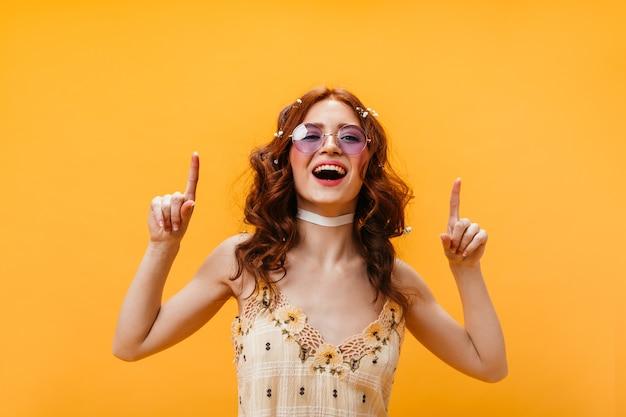 ポジティブな女性は指を上に向けます。黄色のトップとオレンジ色の背景にポーズをとる薄紫色のメガネの女性。