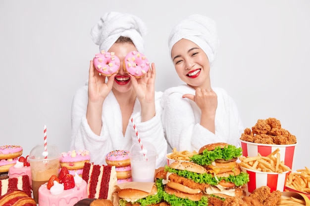Positive woman points at her funny female friends who keeps delicious doughnuts over eyes as if goggles.
