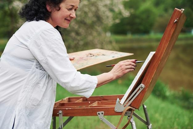 긍정적 인 여자. 야외 공원에서 검은 곱슬 머리를 가진 성숙한 화가의 초상화