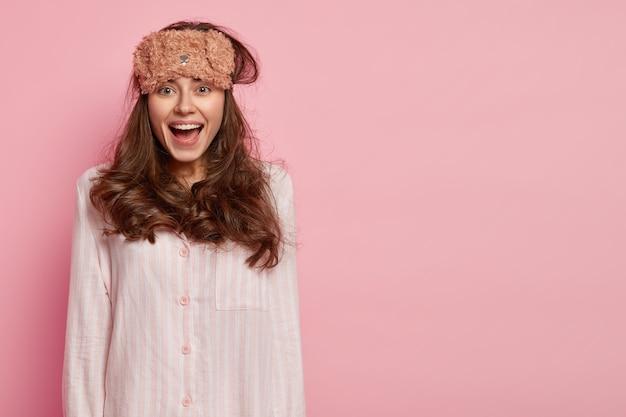 Positive woman prepares for sleep at night, wears sleepmask