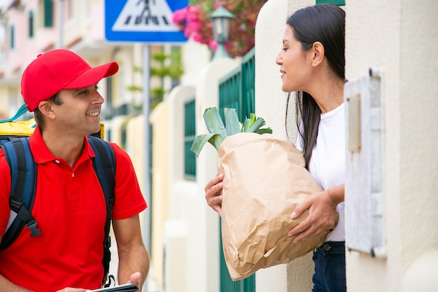 Positive woman receiving food from grocery store, holding paper package with green vegs ad thanking courier in red uniform. shipping or delivery service concept