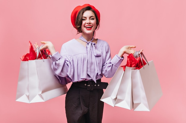 Positive woman in red beret and trendy blouse smiles and holds bags from clothing stores.